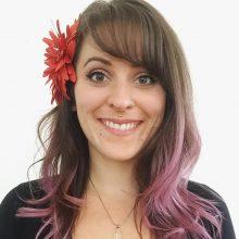 Kelly Schott, Headshot with flower behind right ear.