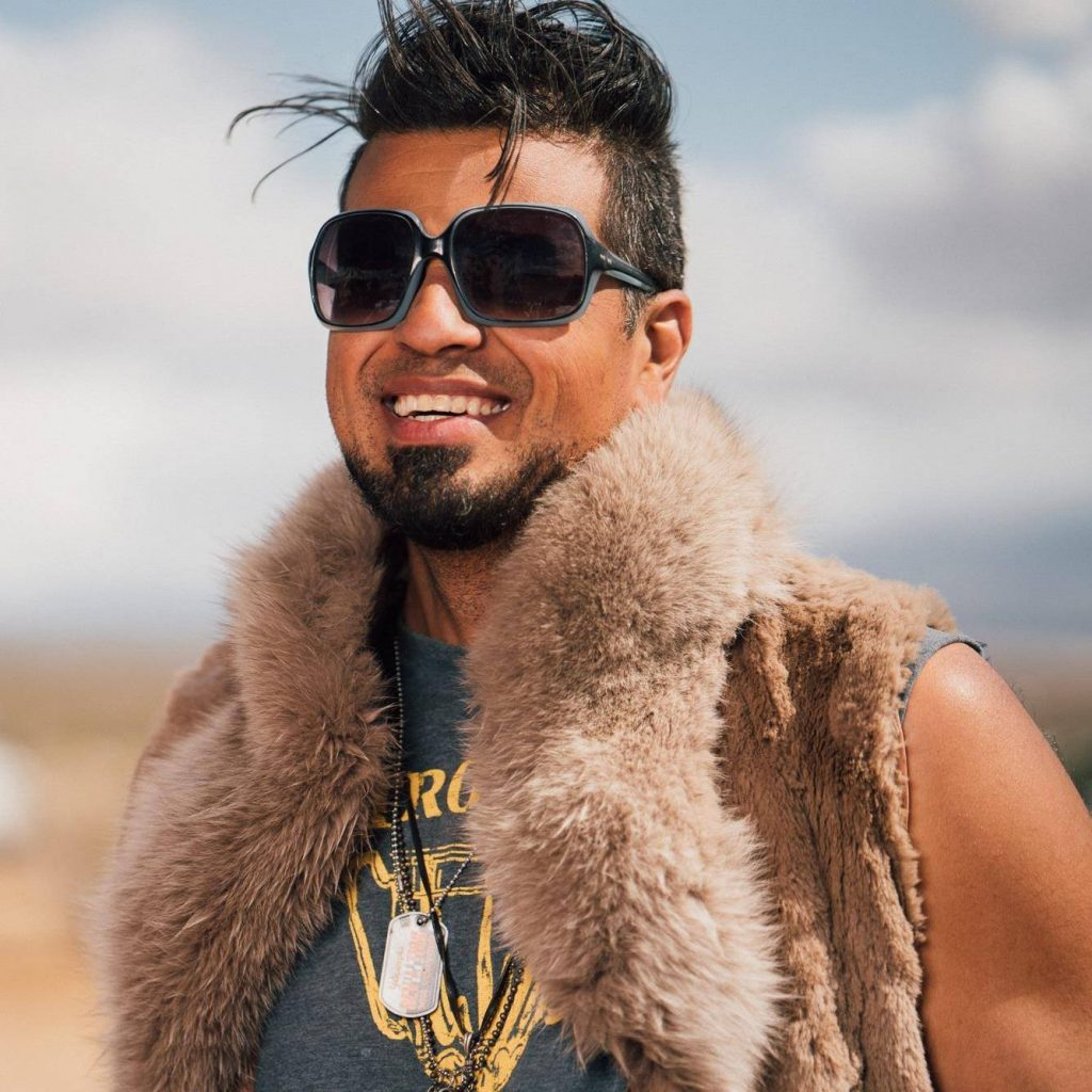Arash Afshar Founder of Justified Hype at a festival smiling wearing large sunglasses