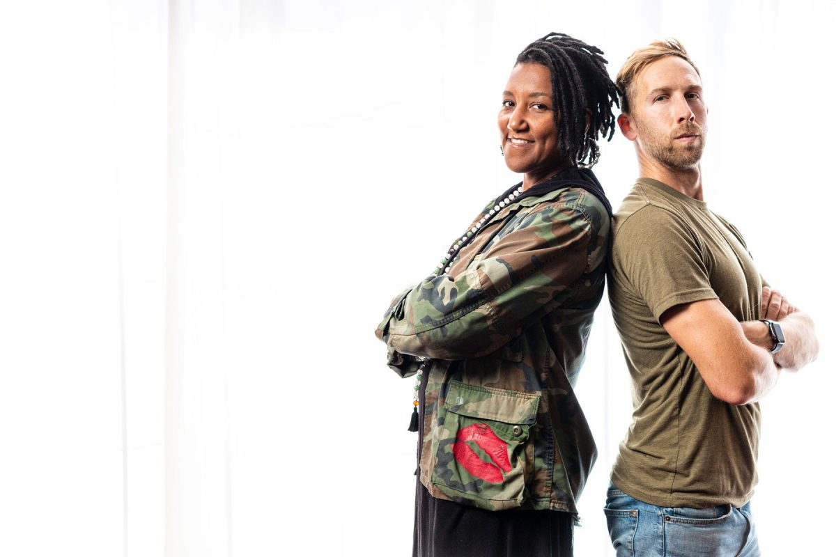 Miki Vale and Nick Isabella standing back to back with arms crossed, on a white background. Miki on the left wearing a camo jacket and Nick on the right wearing a brownish green shirt. They present as a power duo for this month's About The Cover.
