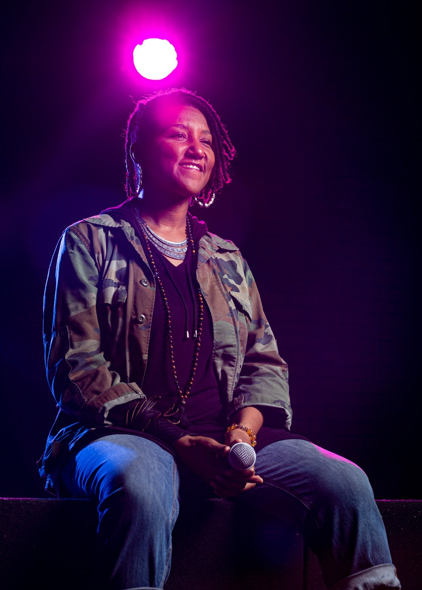 Miki Vale sitting on the edge of the stage with a smiling face. She's wearing a camo jacket and she's holding a microphone with both hands.