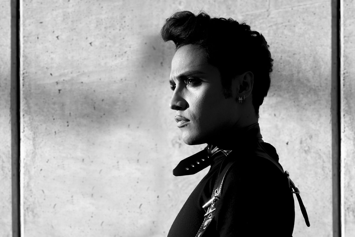 B&W portrait of young man in leather jacket against cement wall profile view.