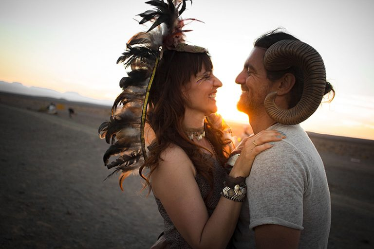 Afrika Burn 2019 horned man and woman in feather headdress in embrace at sunset. photo by Arash Afshar
