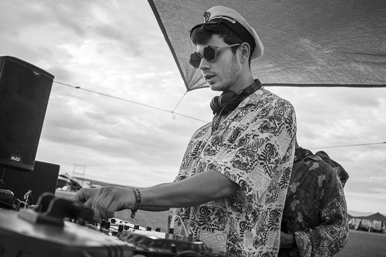 B&W of a dj at work wearing a captain's cap Afrika Burn 2019 photo by Arash Afshar