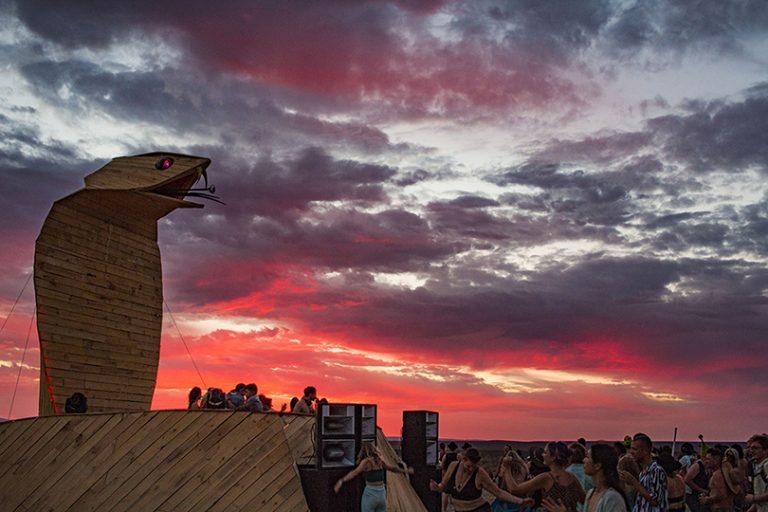 Wooden Cobra art car at sunset with fire sky AfrikaBurn 2019 photo by Arash Afshar