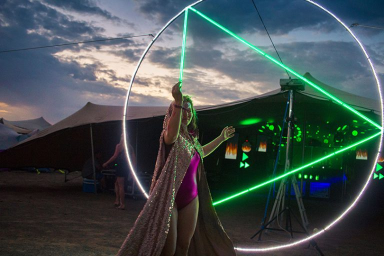 Afrika Burn 2019 woman carrying large round and triangle light object at AfrikaBurn 2019 photo by Arash Afshar