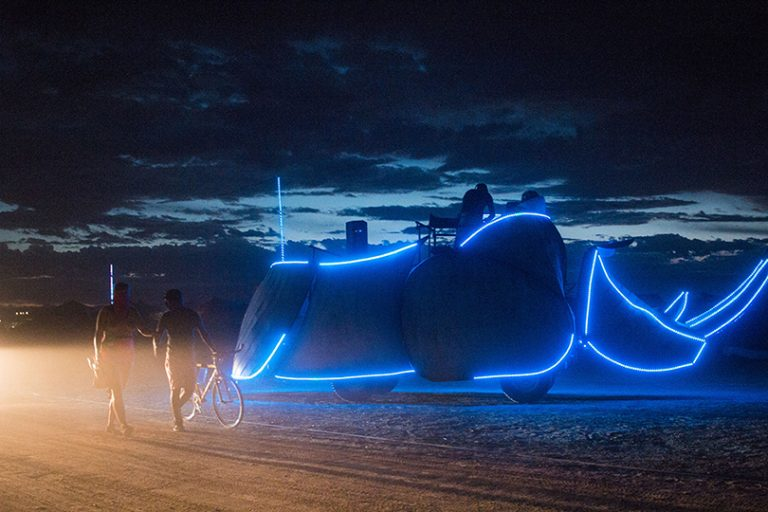 Afrika Burn Rhino art car lit up in blue early evening photo by Arash Afshar