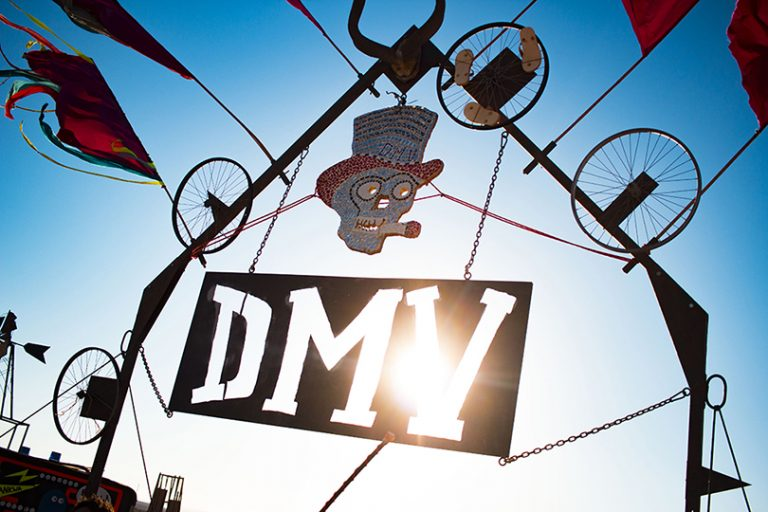 Afrika Burn 2019 sun coming through a sign that reads DMV. photo by Arash Afshar
