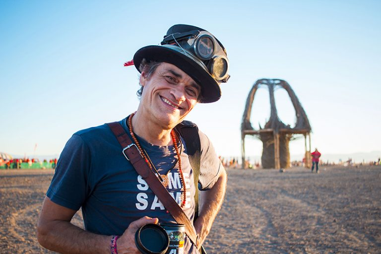 Afrika Burn 2019 male photographer in top hat and goggles poses with effigy in background photo by Arash Afshar