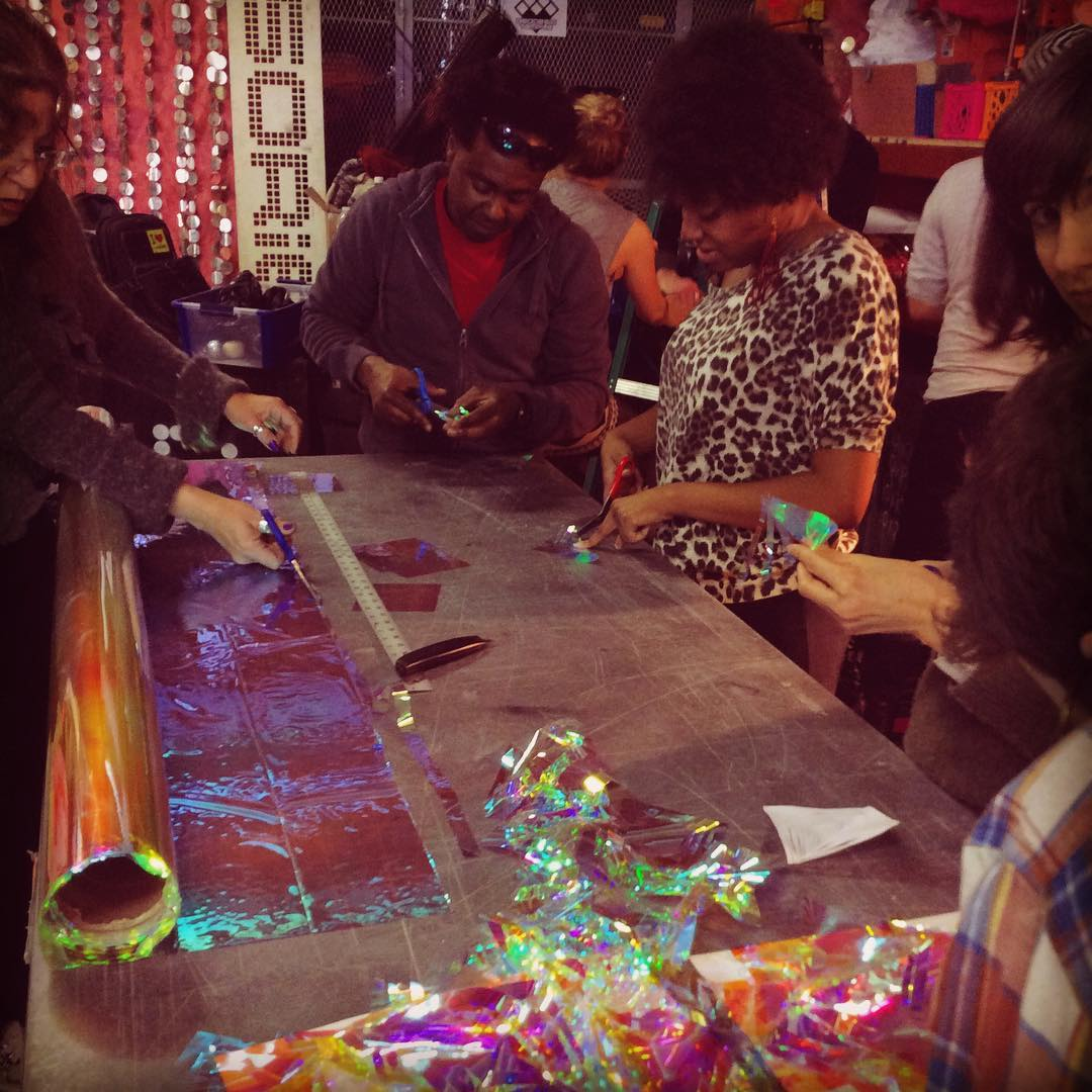 People at a working table making art with metallic xelophan paper