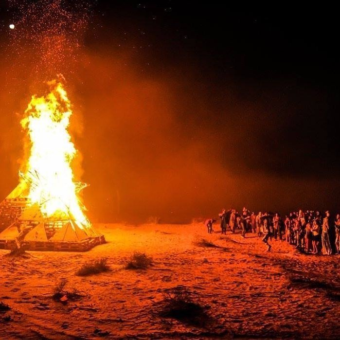 Burning structure at night,; people dancing and enjoying the flame at a decent distant