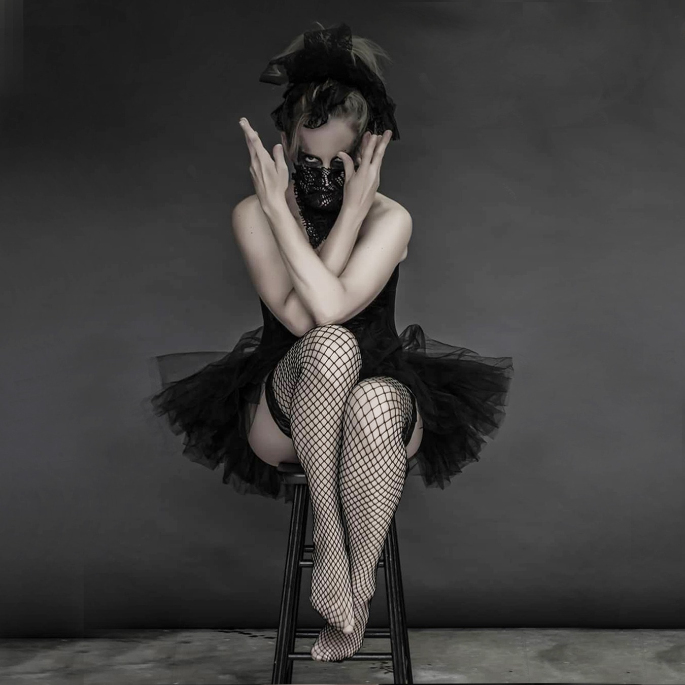 Ballerina sitting on a high chair, wearing a black tutu skirt with black corsage; covering her mouth with a screened scarf and with both arms crossed near her face forming a V