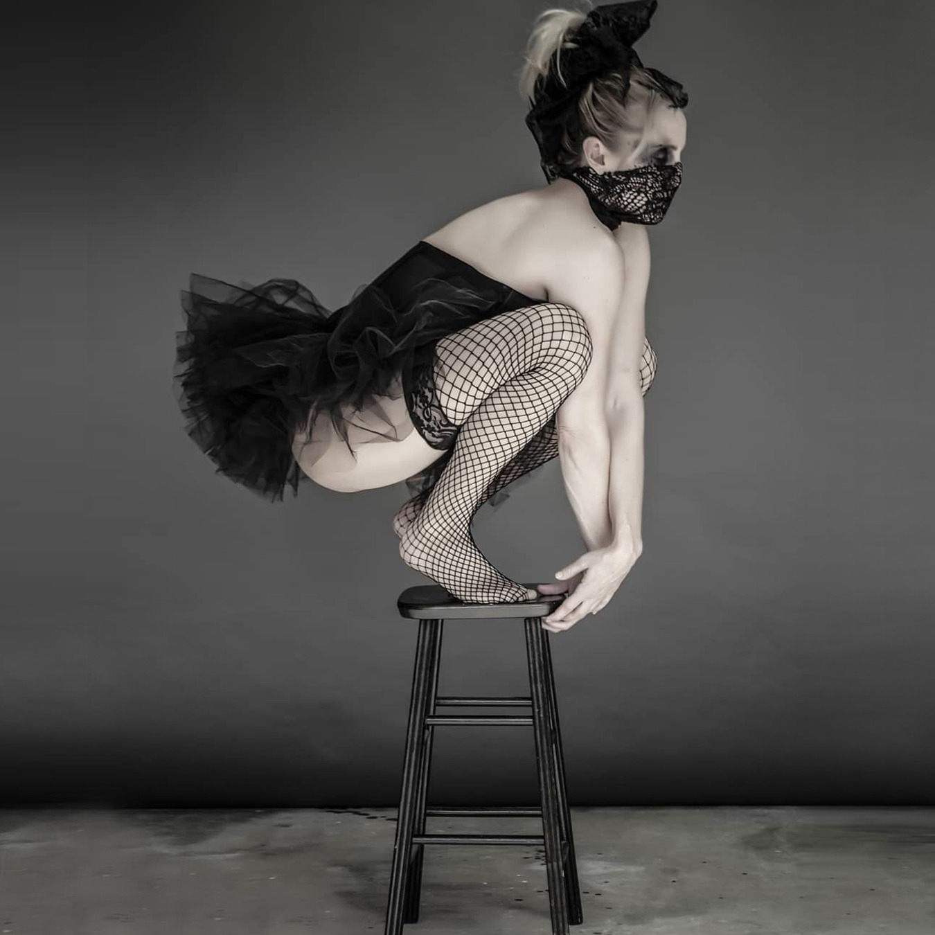 Ballerina standing on a frog position on top of a high chair, wearing a black tutu skirt with black corsage; covering her mouth with a screened scarf