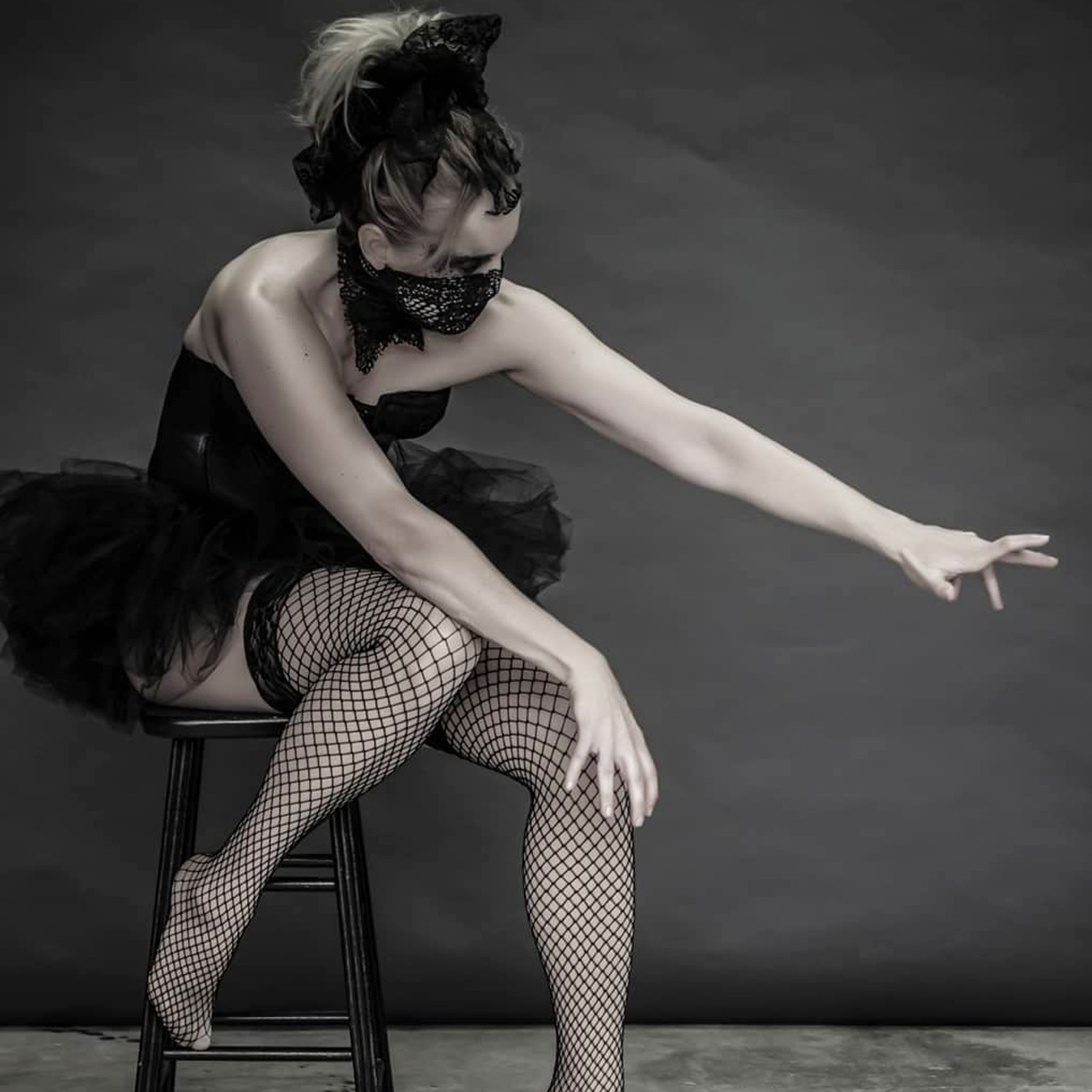 Ballerina sitting on a high chair with her left foot on the ground, wearing a black tutu skirt with black corsage; covering her mouth with a screened scarf and looking likes she is trying to reach something on the ground