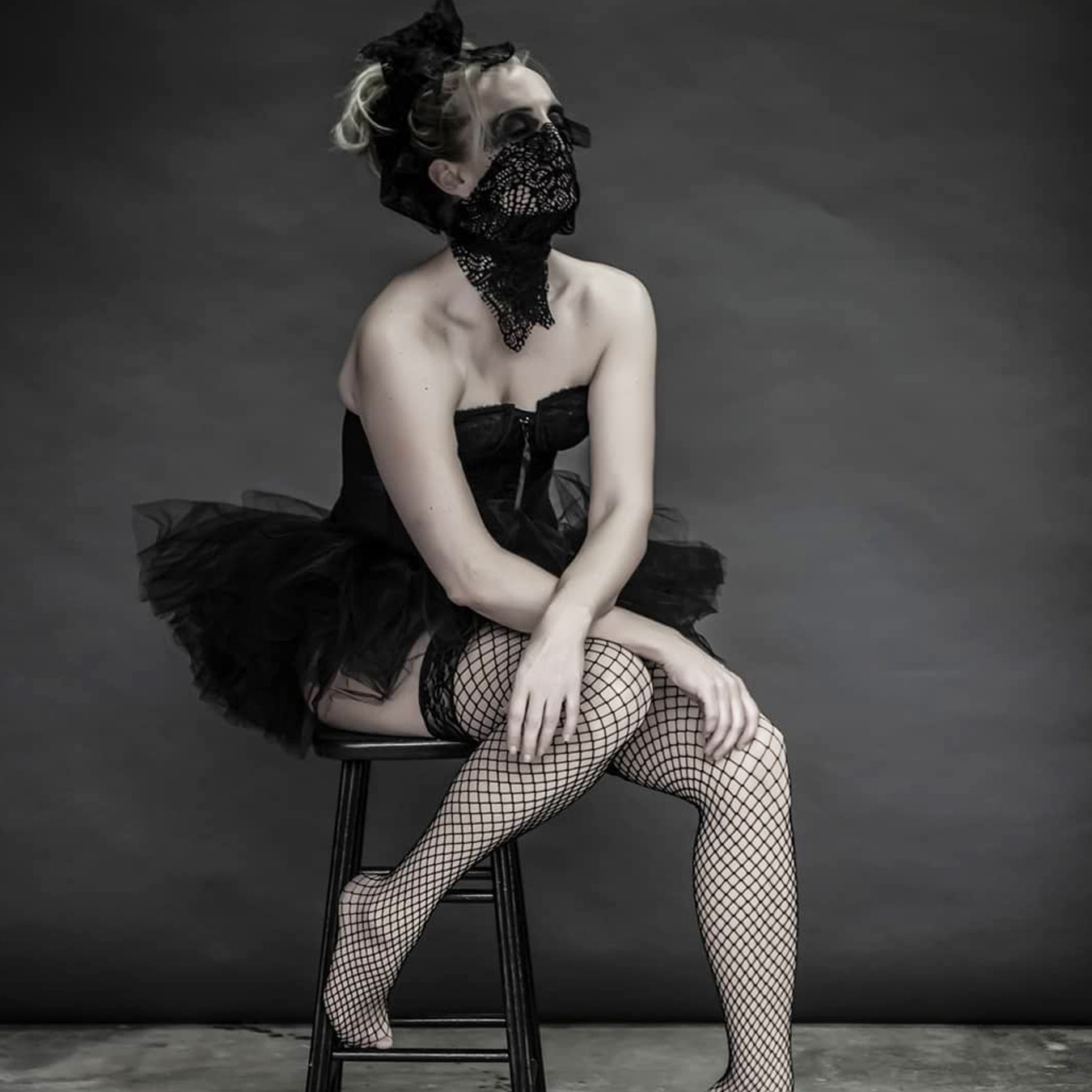 Ballerina sitting on a high chair with her left foot on the ground, wearing a black tutu skirt with black corsage; covering her mouth with a screened scarf looking up like waiting for something to happen