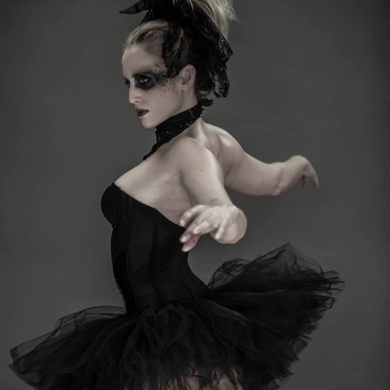 Ballerina with arms spread dancing back to the camera, wearing a black tutu skirt
