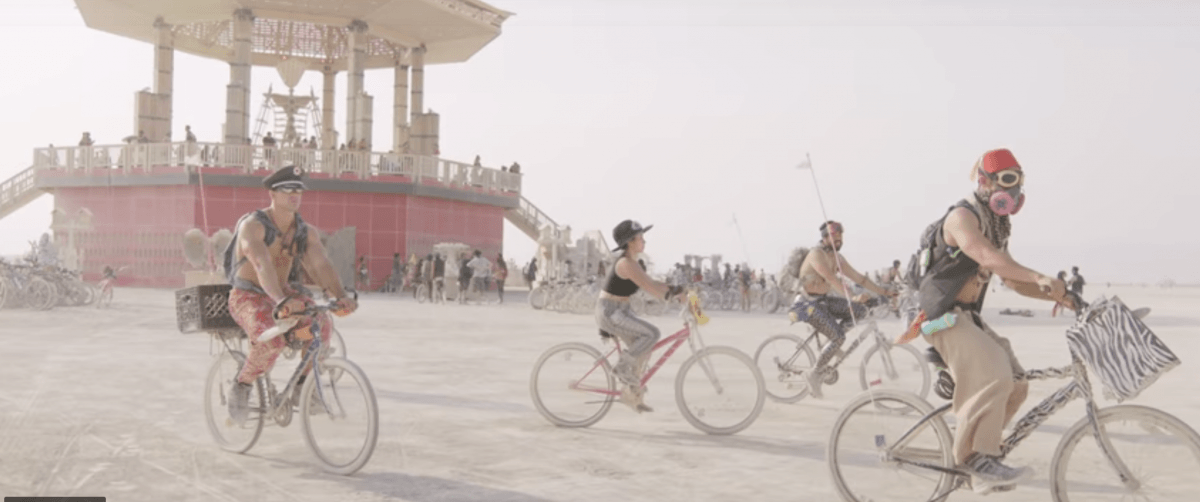 People riding bikes at Black Rock City near the temple; Burning Man