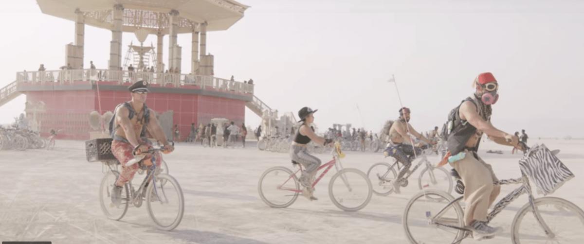 People riding bikes at Black Rock City near the temple; Burning Man