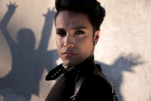 Creator Adan Guerra looking at the camera with dancing shadows behind him