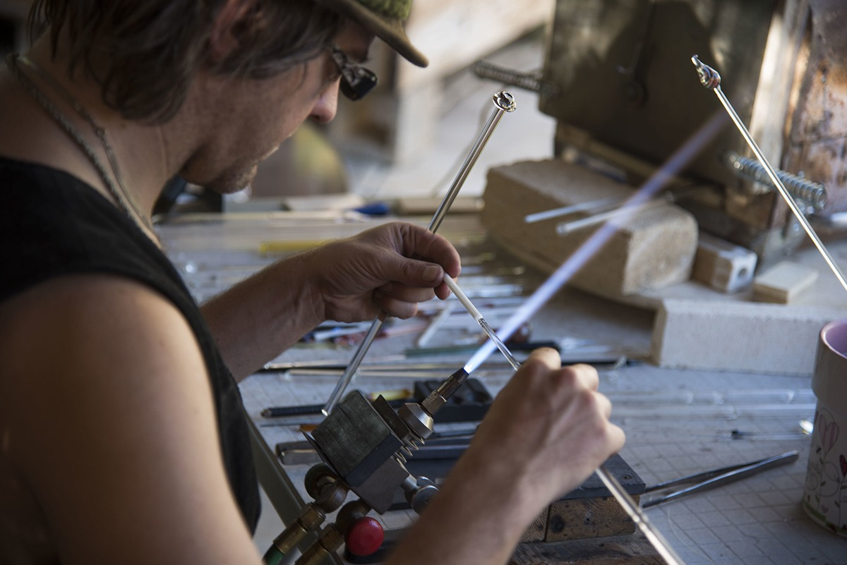 Glass artist Corey Mitchell is holding a thin glass tube against the blow torch flame.