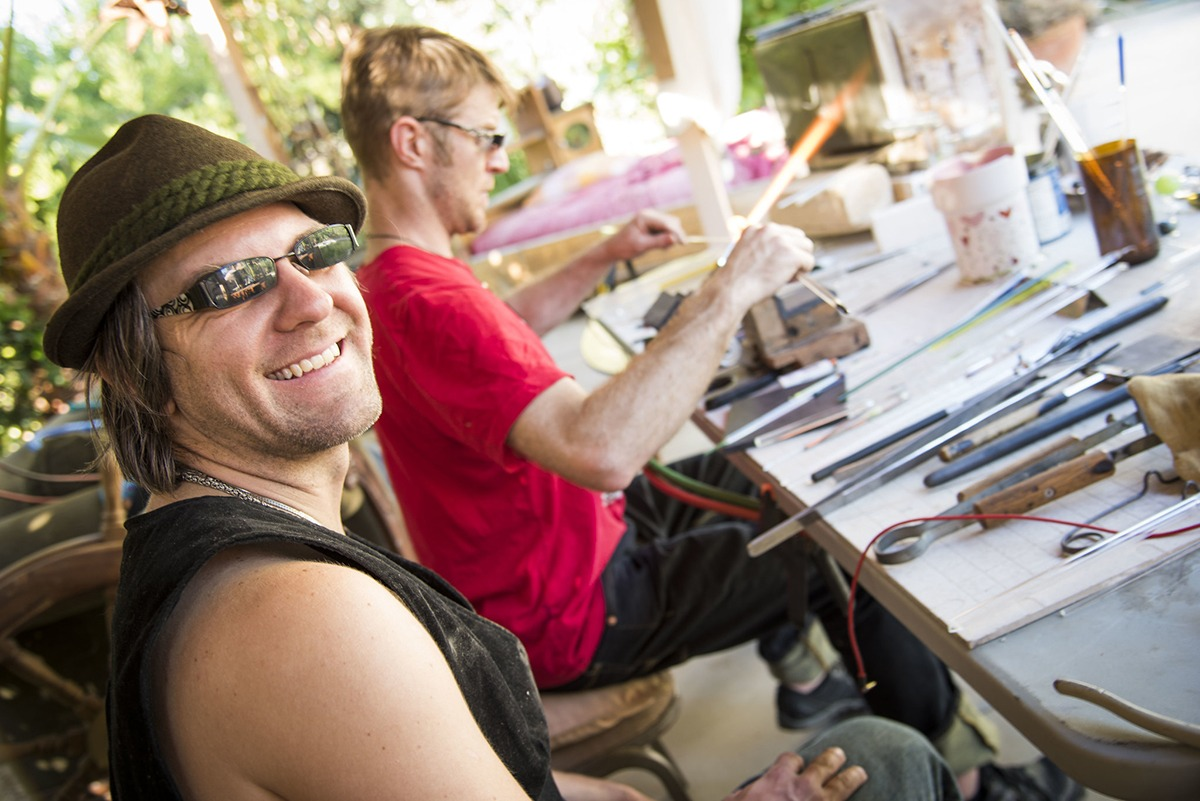Glass artists Corey Mitchell smiling at the camera while Alexander Chacona is working very concentrated in the background; glass tube on the flame taking it's next form