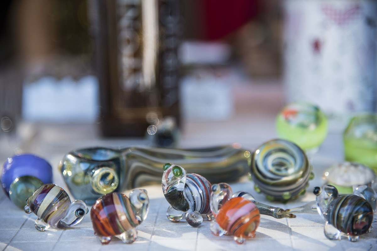 Close-up of small blown glass figurines of turtles and pipes.