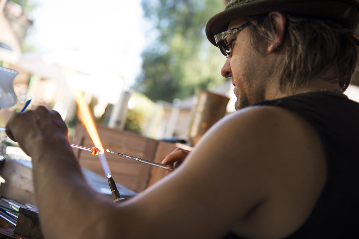 Glass artist Corey Mitchell sitting on the right of the frame, holding two pieces of glass, almost touching themselves right at center on the flame of the blow torch.