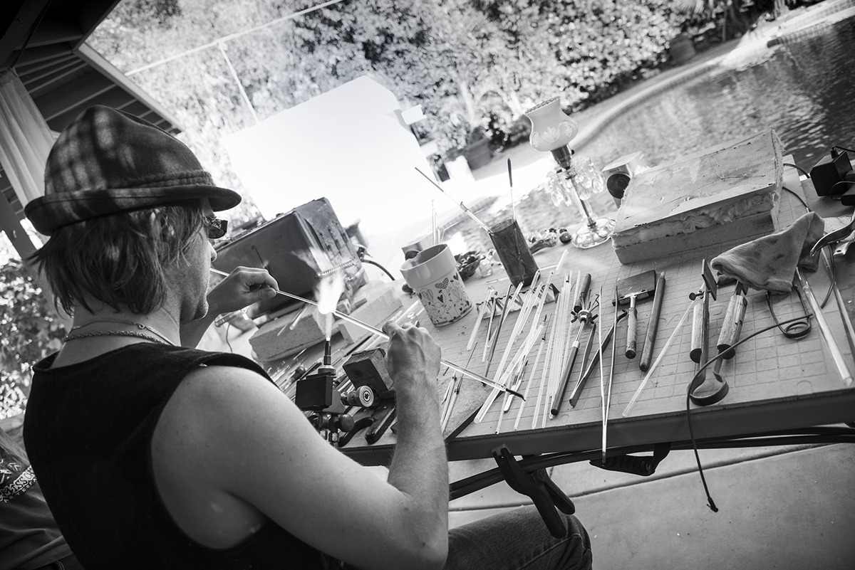 B & W shot of glass artist Corey Mitchell, giving a new form to a tube of glass on a torch flame.