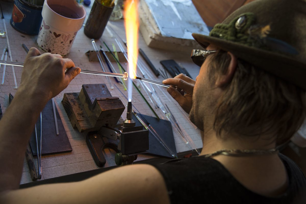 Aerial shot of glass artist, Corey Mitchell doing his art; tool set on the table, a couple of thin glass tubes and a furious flame forming and molding the piece of glass.