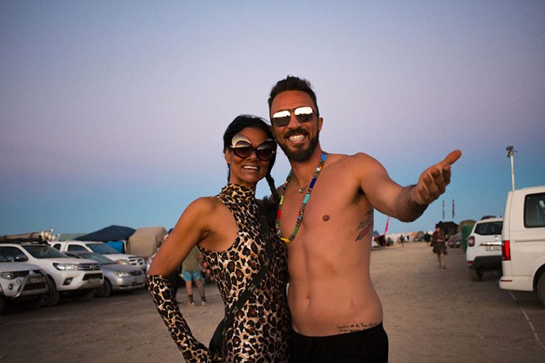 Attendees smiling at camera; photo from AfrikaBurn 2019 of a jubilant woman dancing by herself. AfrikaBurn 2019 photos by Arash Afshar
