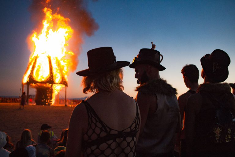 Effigy Burn in background, event attendees in foreground. AfrikaBurn 2019 photos by Arash Afshar