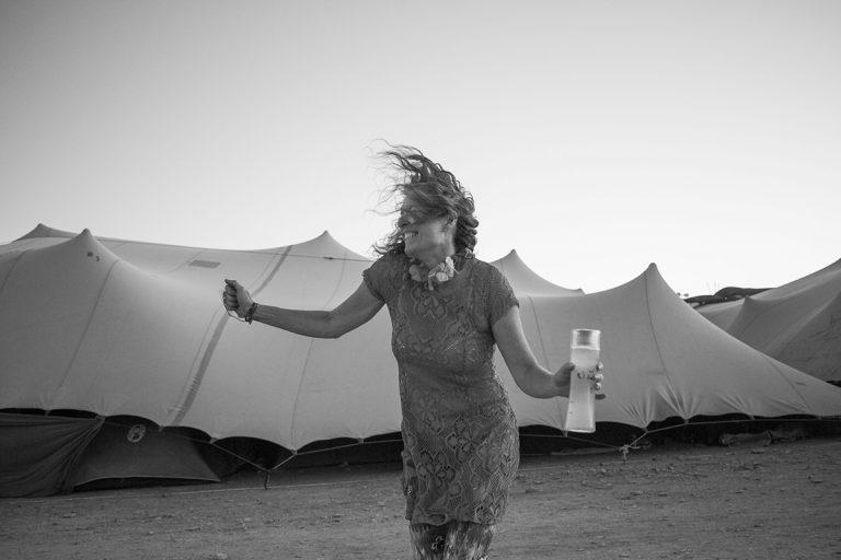 B&W photo from AfrikaBurn 2019 of a jubilant woman dancing by herself. AfrikaBurn 2019 photos by Arash Afshar