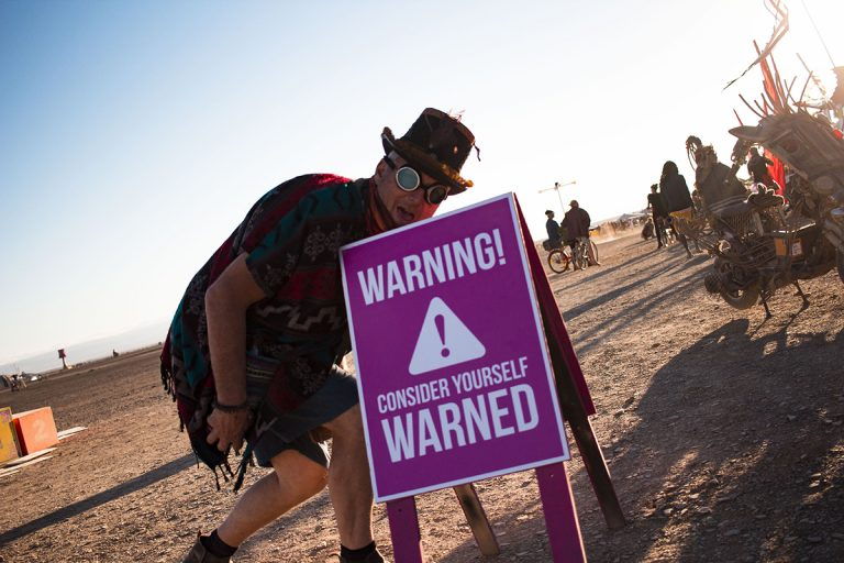 Event attendee crouching behind a sign reading Warning Consider Yourself Warned AfrikaBurn 2019 photos by Arash Afshar