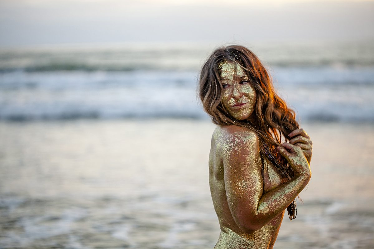 Golden woman at the shoreline, pleasantly looking back over her shoulder towards land. From the Secrets of the Stars series photos by Jon Medel